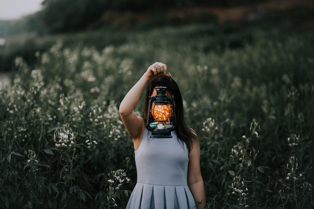 woman in gray dress holding kerosene lamp
