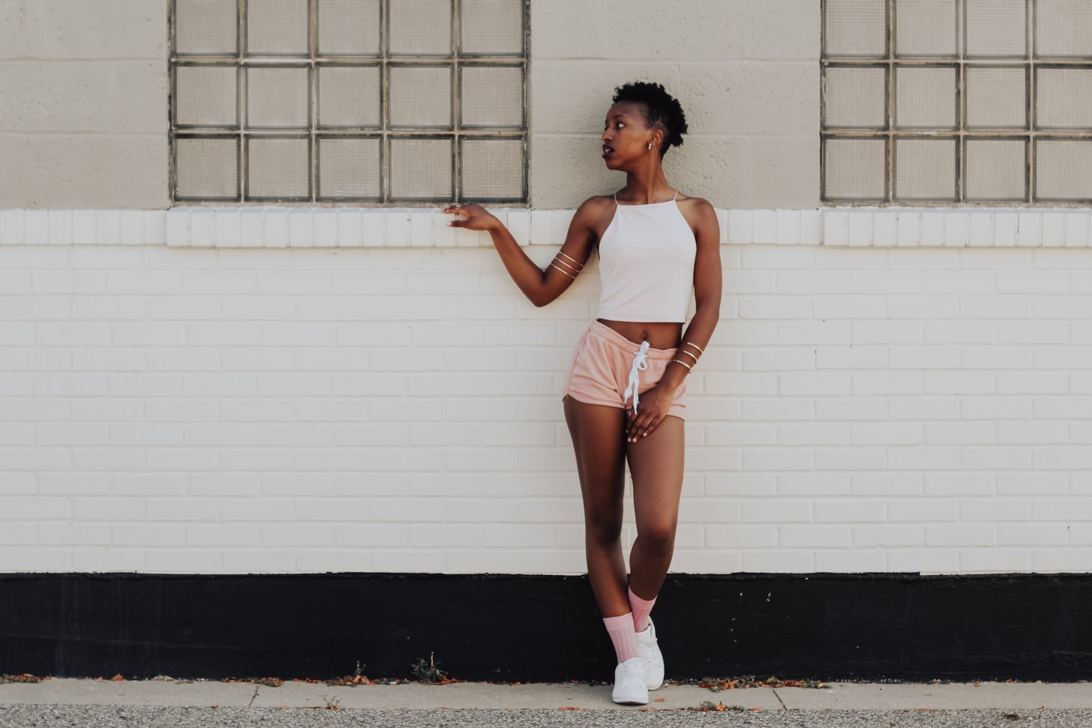woman wearing white crop top and leaning on wall