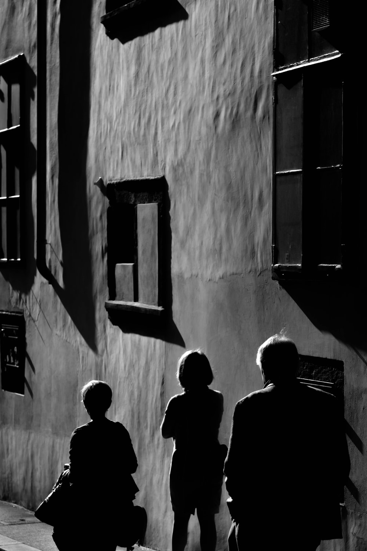 three persons walking near gray wall