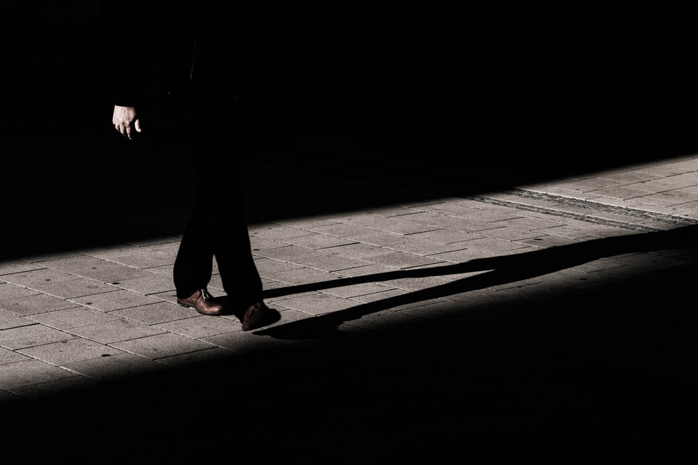 person walking on narrow pathway with shadow on gray floor