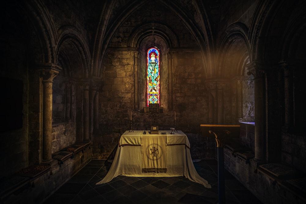 white table near brown wall inside church