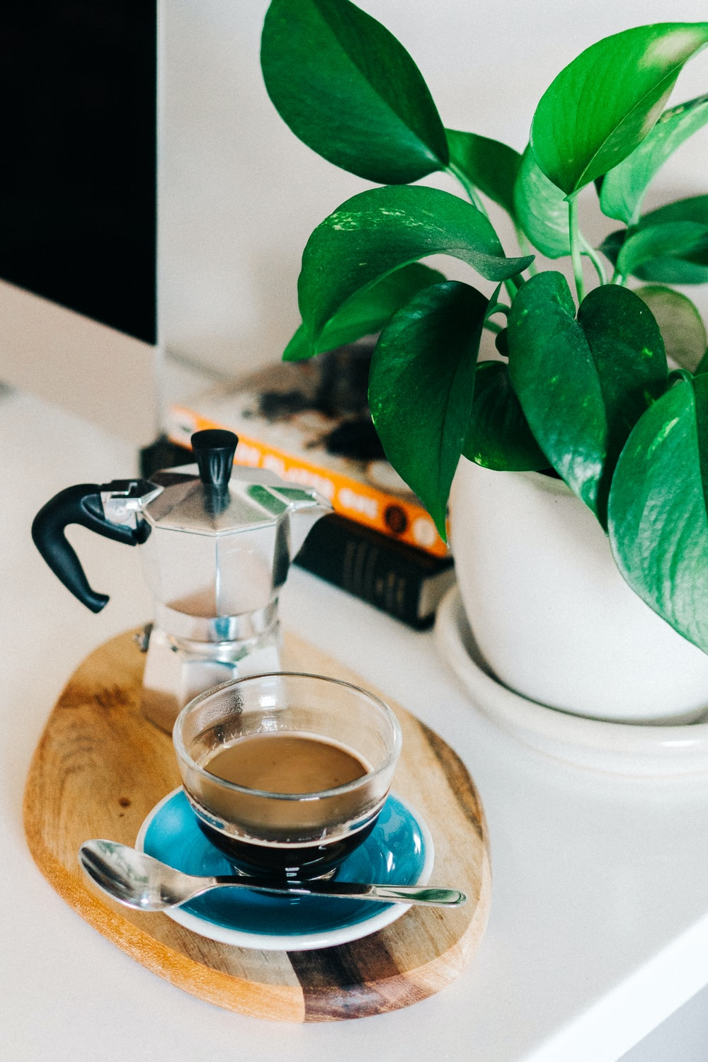 teacup filled with coffee beside moka pot