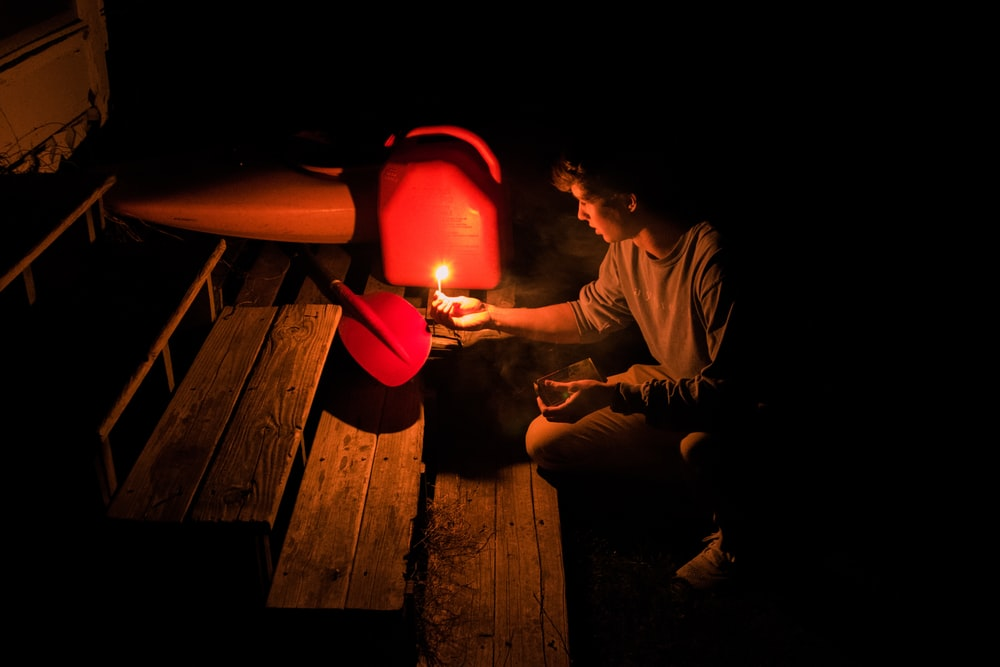 person holding candle lighting the red and black metal part in dark room near ladder