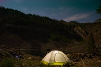white camping tent near the hill