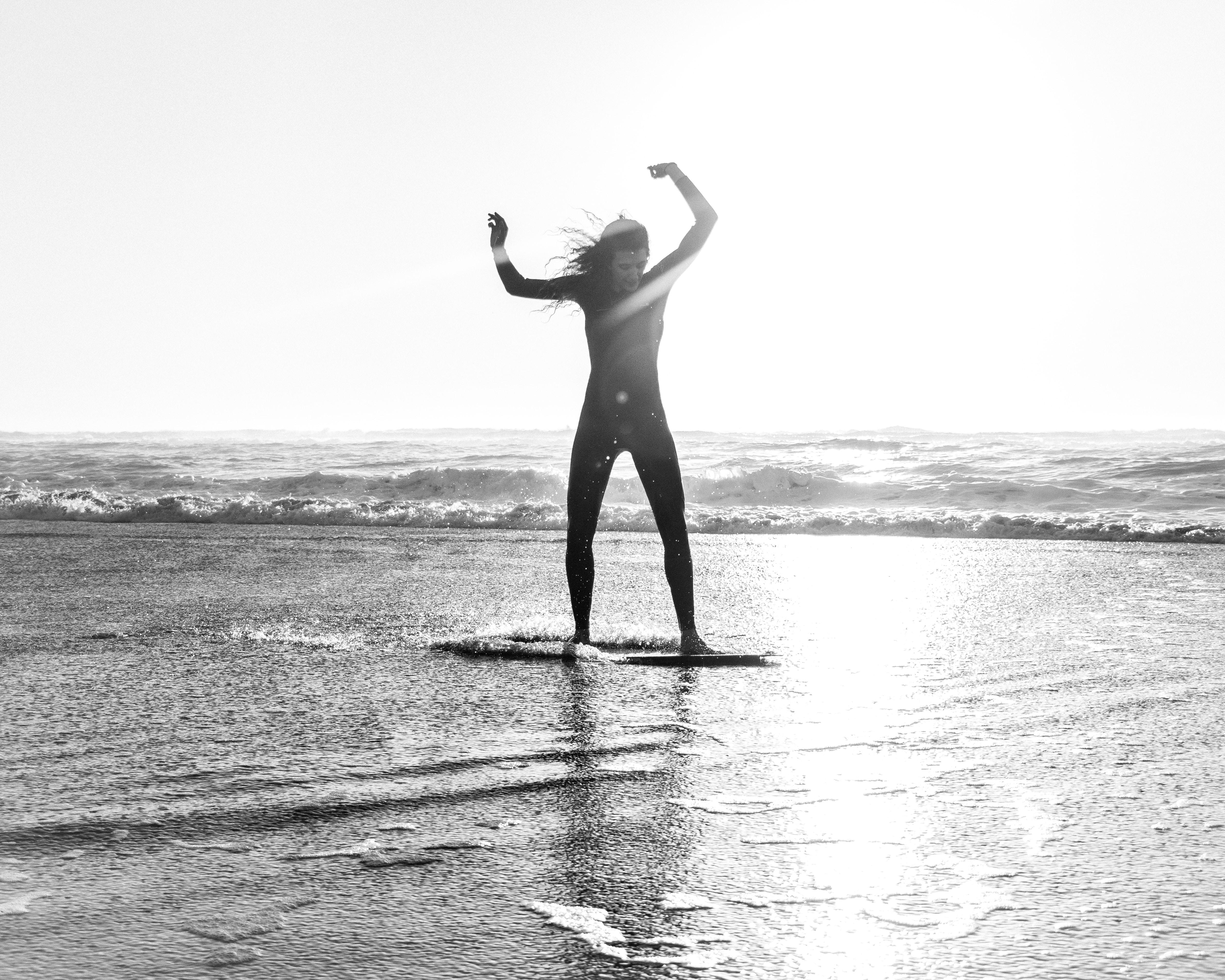 greyscale photo of woman riding skimboard