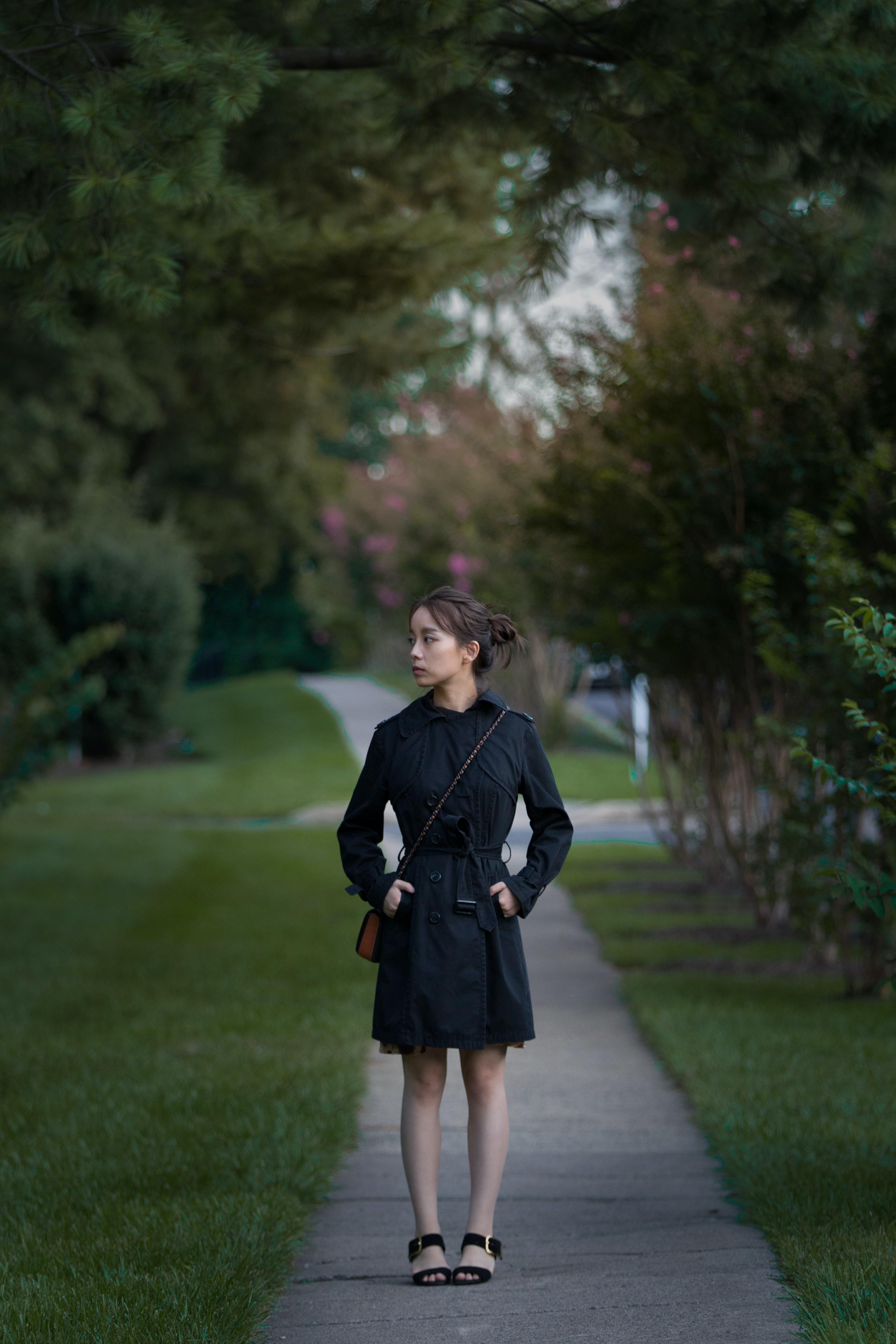 women's black dress shirt standing on pathway