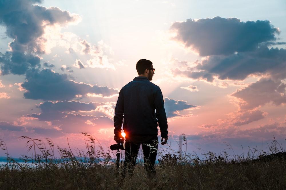 man in black long-sleeved shirt holding DSLR camera standing on grass