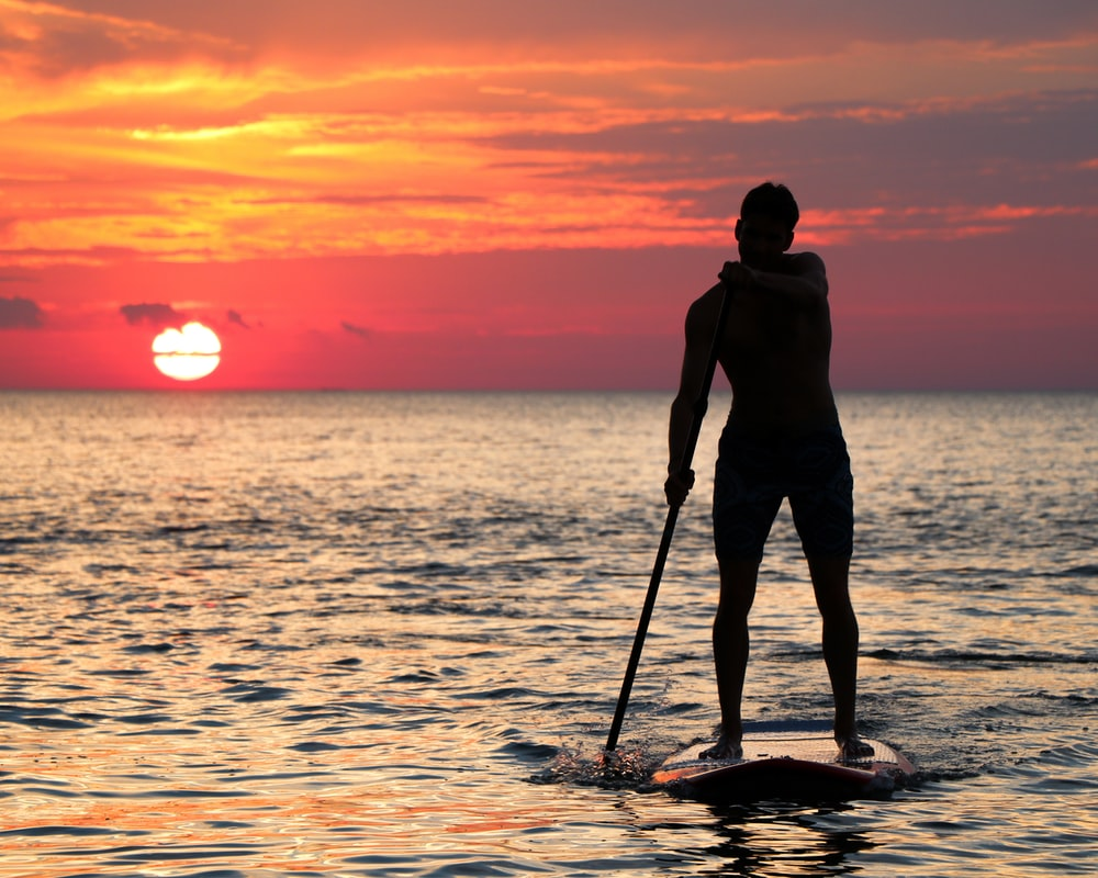 man riding paddleboard silhouette during golden hour