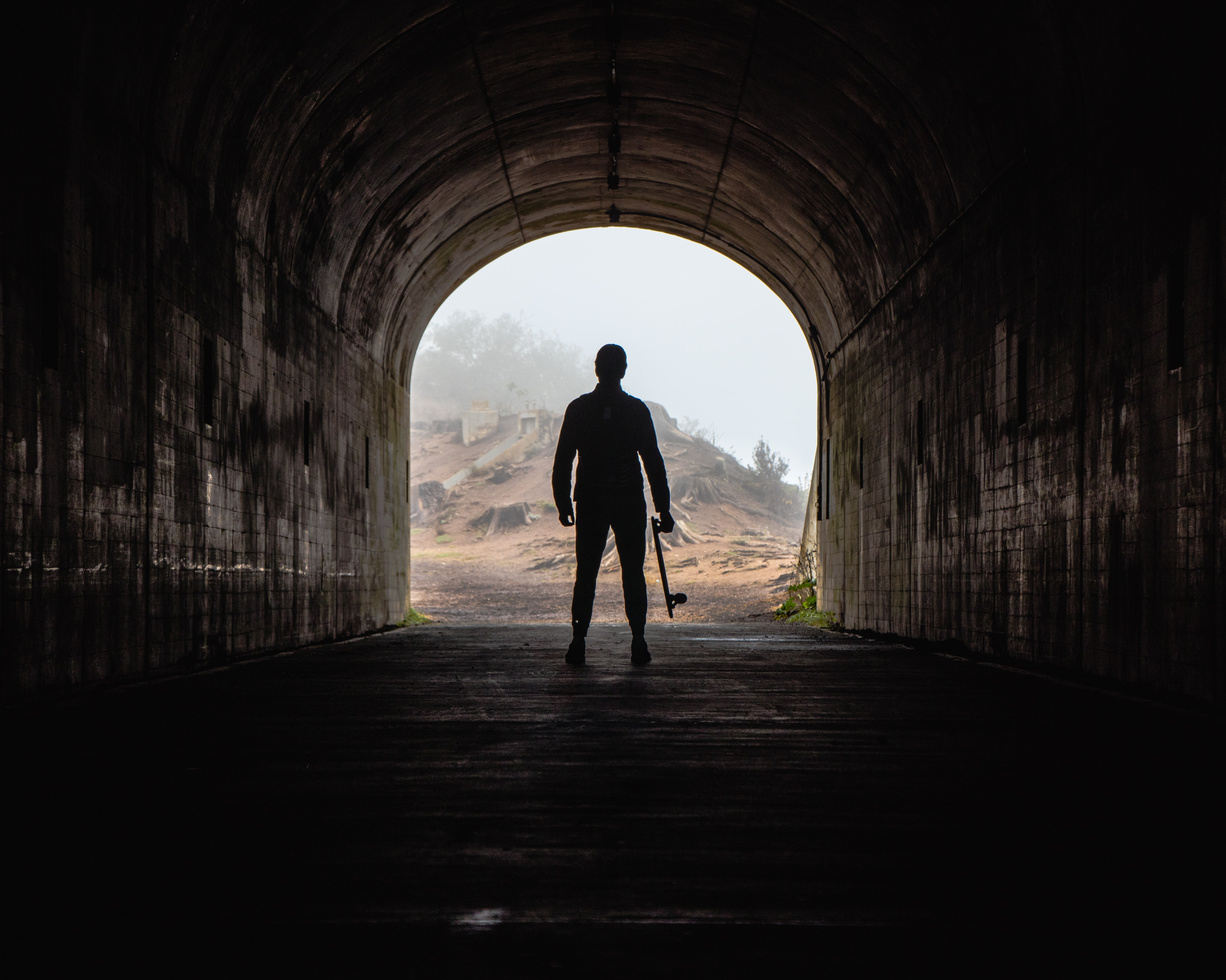 silhouette photo of a man carrying skateboard inside tunnel