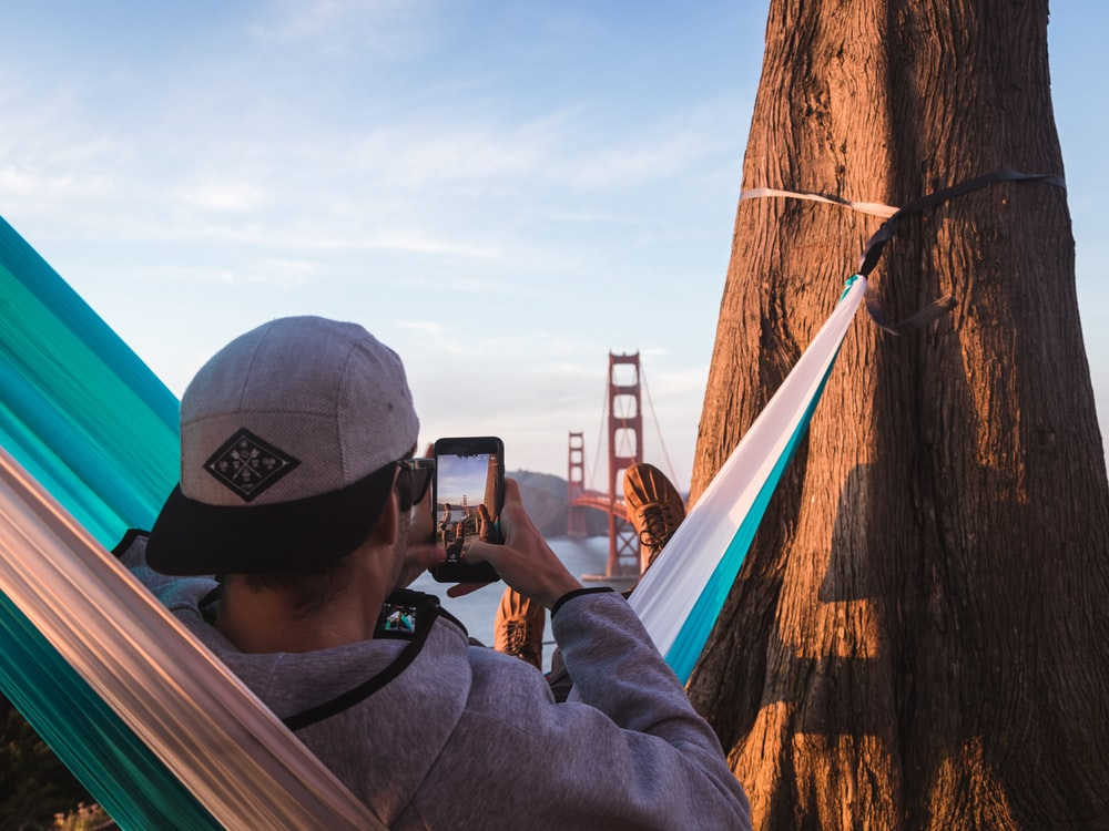 shallow focus photography of man on hammock while taking photo of Golden Gate Bridge of California to his phone
