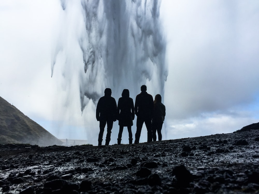 four person's looking at geyser