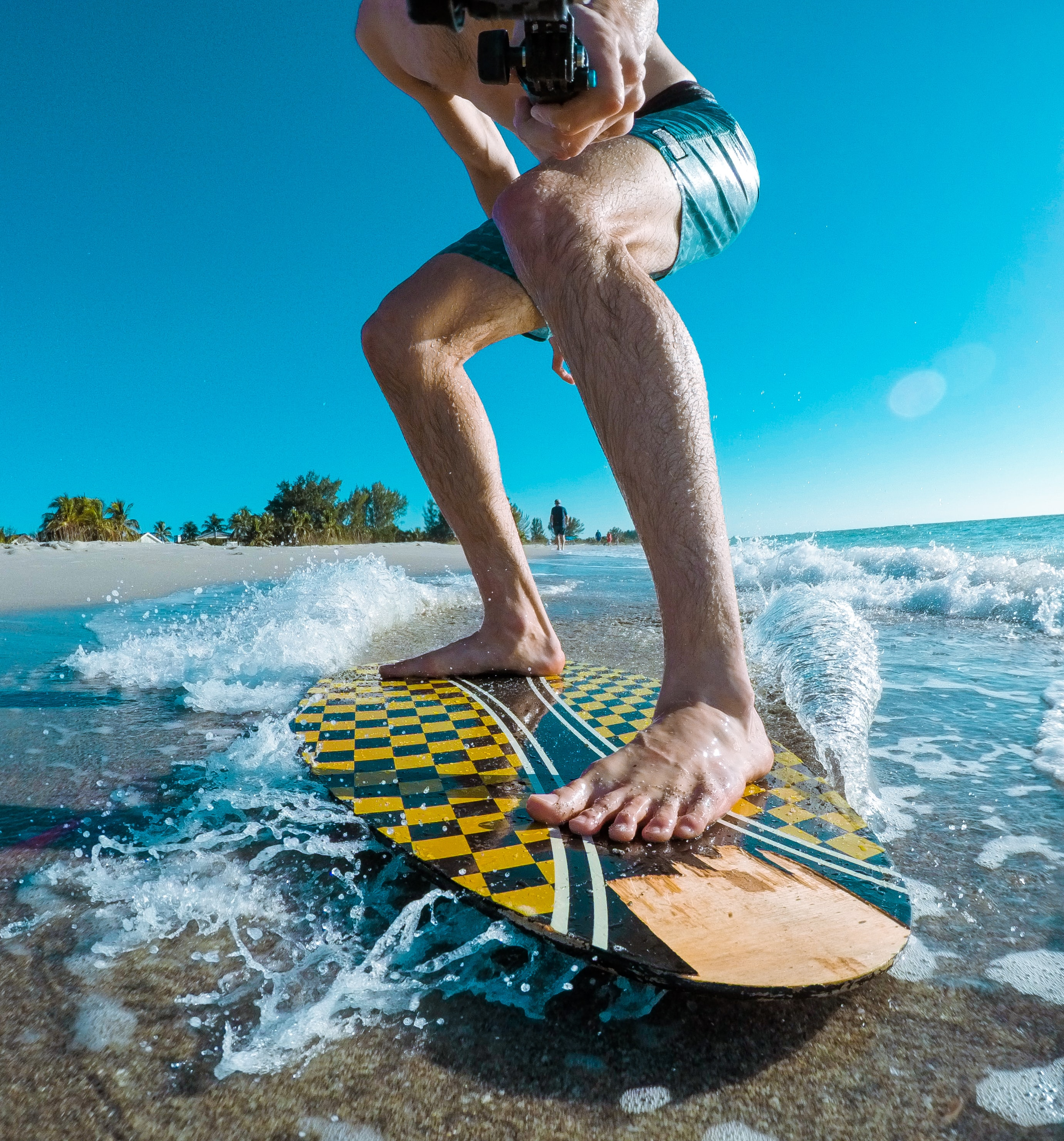 person surfboarding while taking footage of himself on beach during daytime
