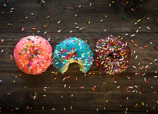 pink, blue, and chocolate with sprinkles doughnuts on table