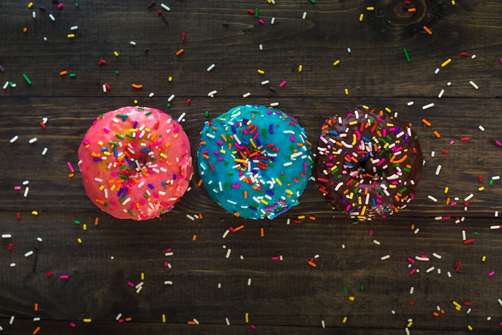 three donuts with sprinkle toppings
