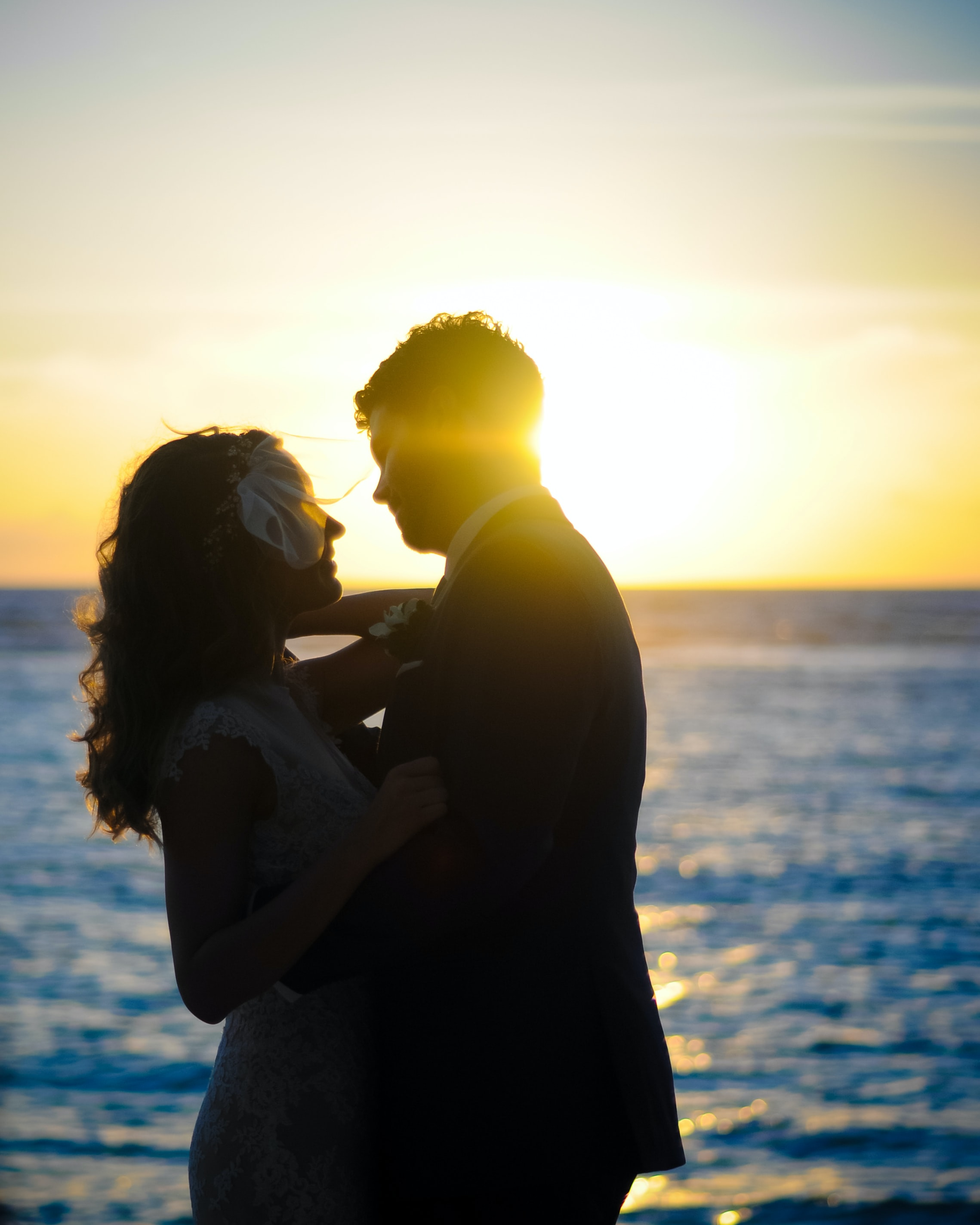 man hugging his wife in front of ocean during daytime