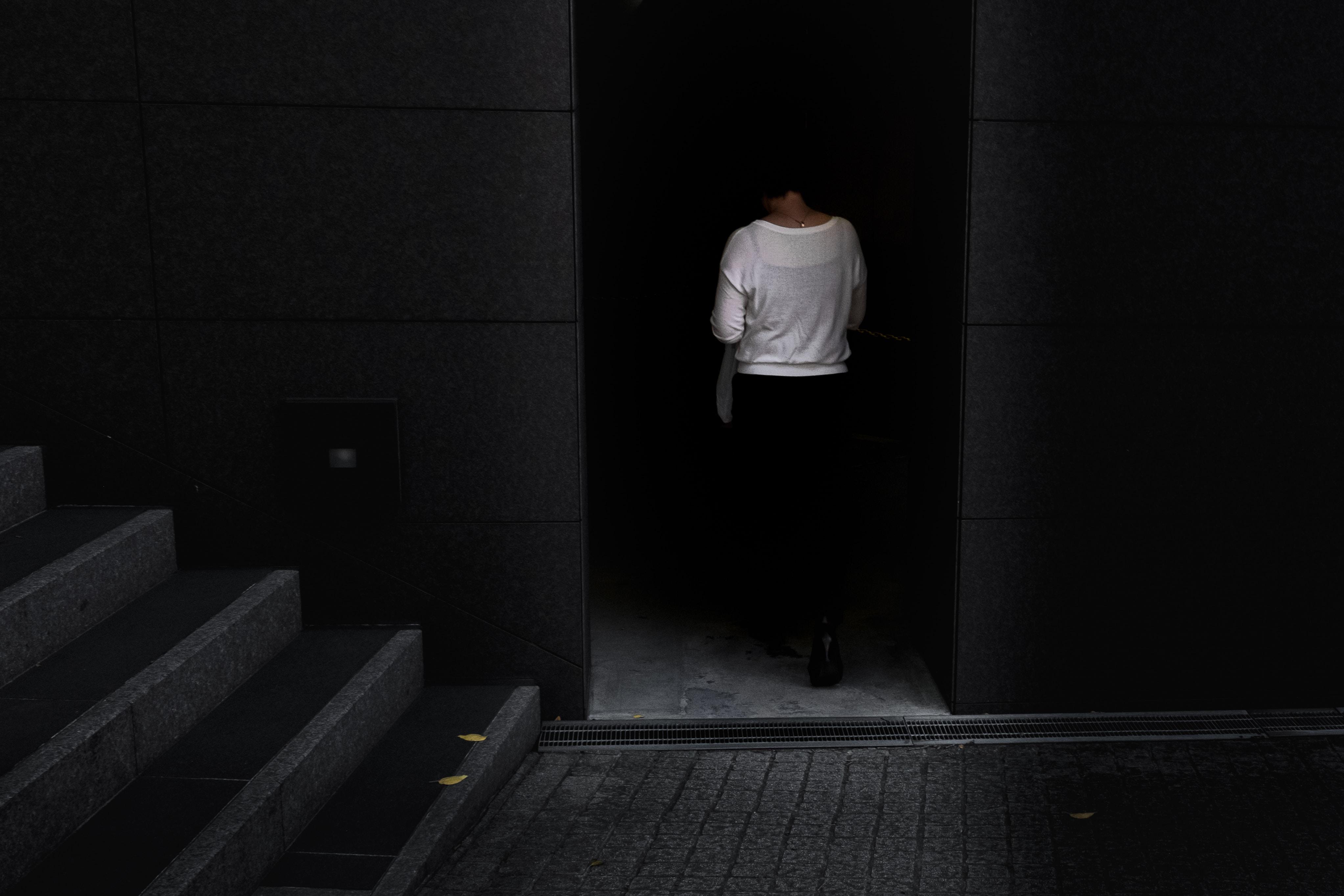 woman walking near gray stair inside building