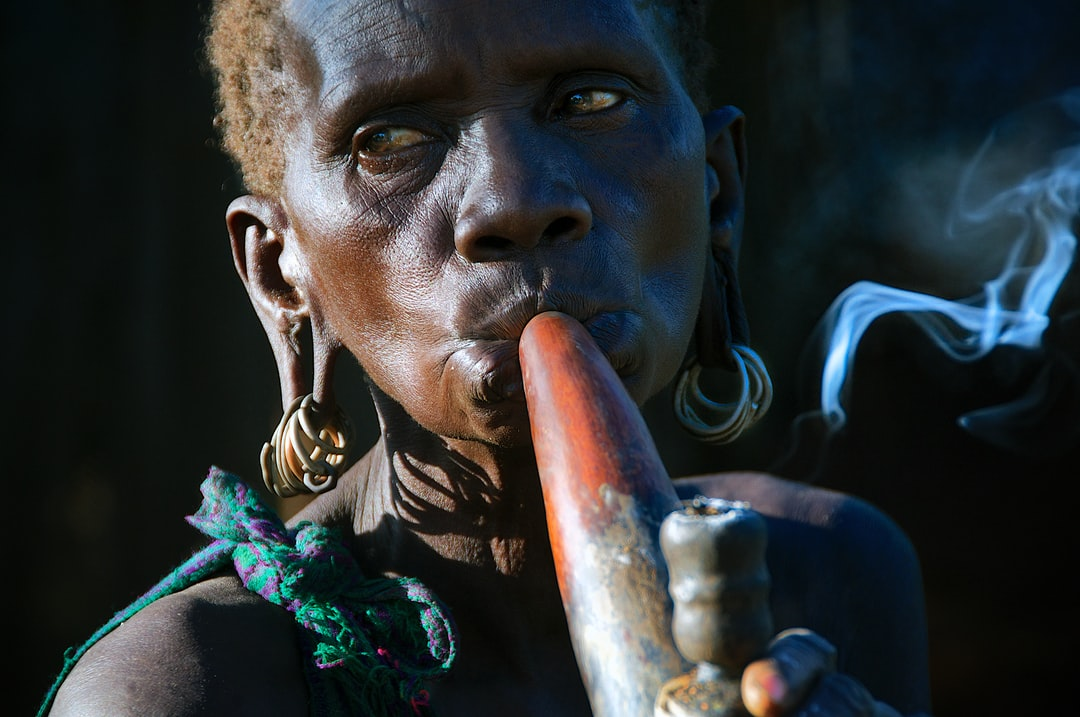 An old Suri woman enjoying her calabash pipe