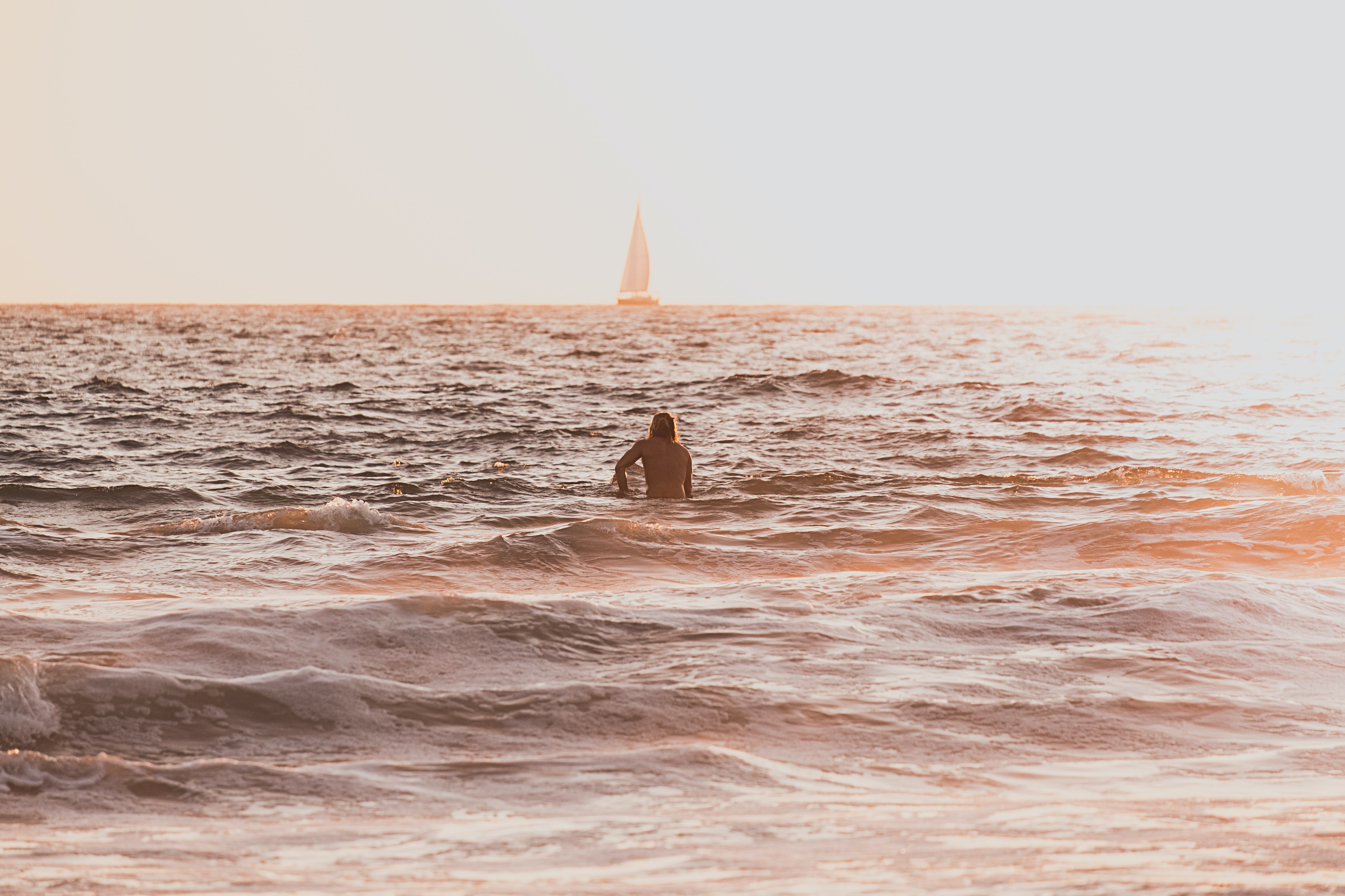 person riding surfboard during golden hour