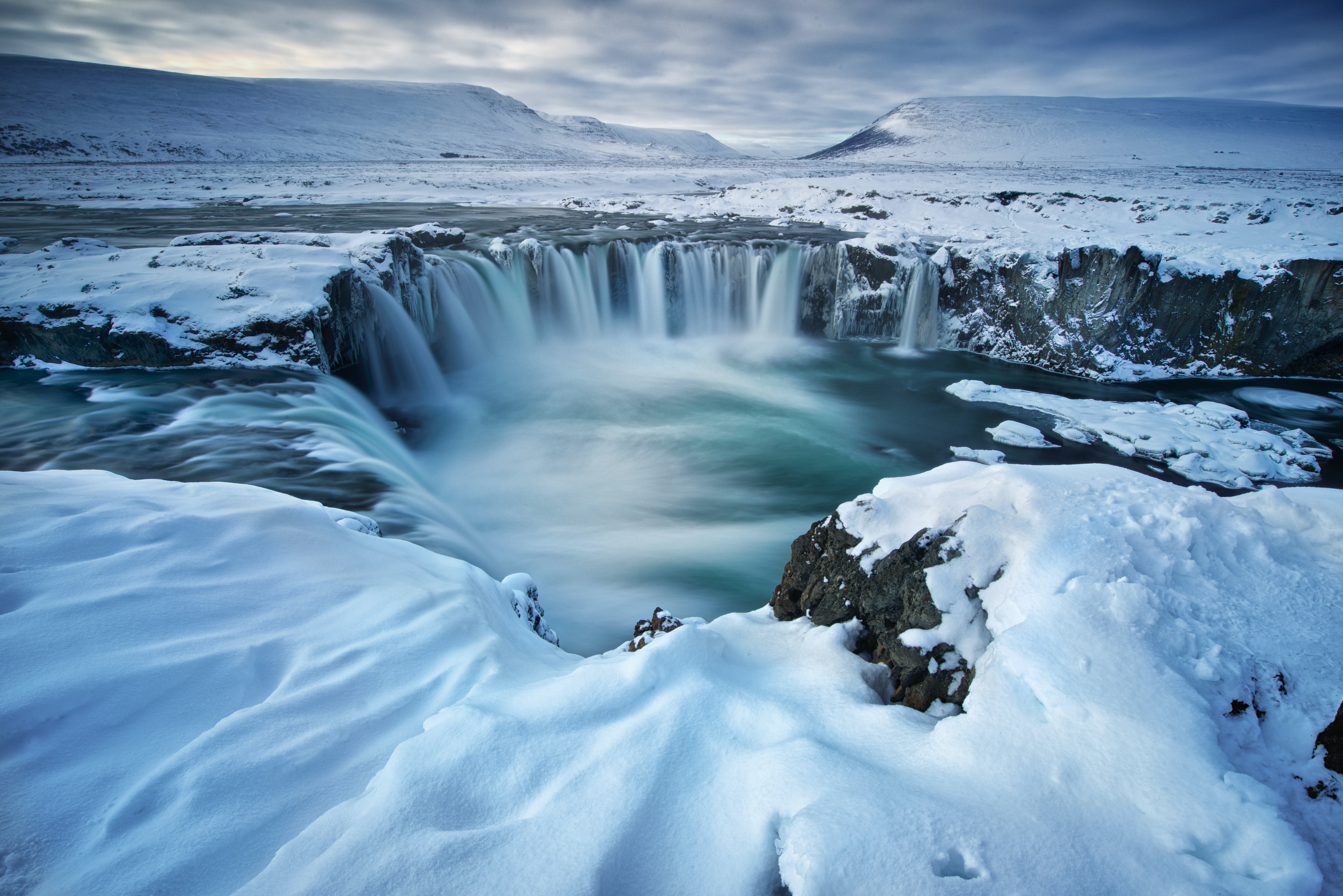 time lapse photography of waterfalls in snow