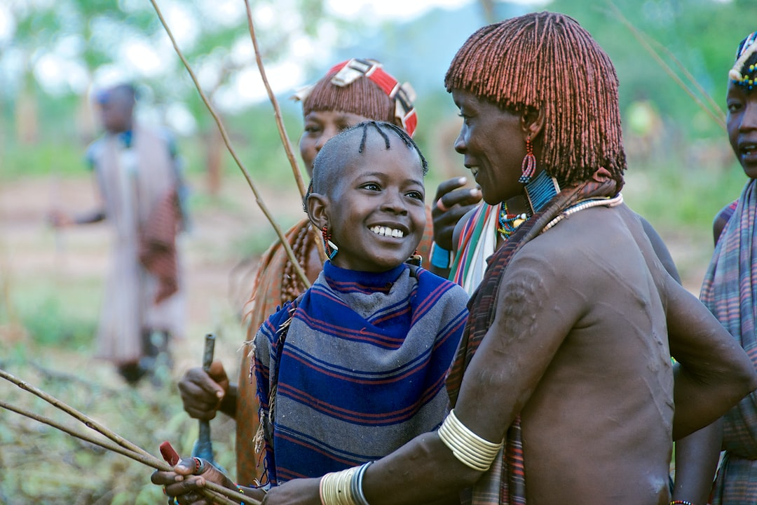 A moment of affection and humour captured between a young girl and an older tribes woman.