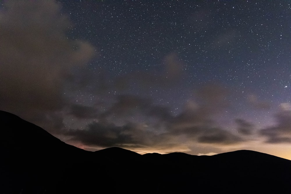 silhouette of mountain under starry sky at sunset