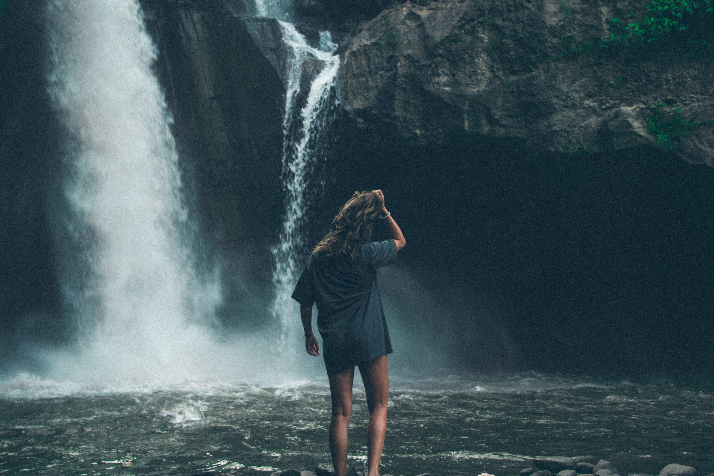 woman standing in front of waterfalls while holding her hair