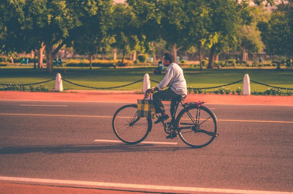 man riding bike on concrete pavement