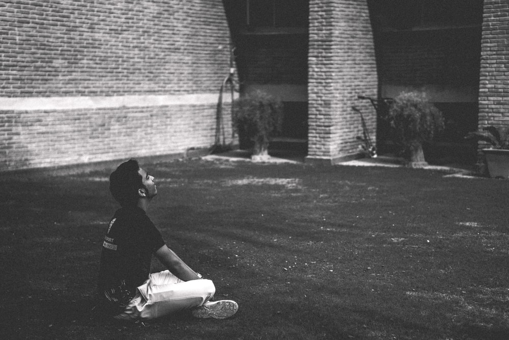 man in black t-shirt sitting on grass