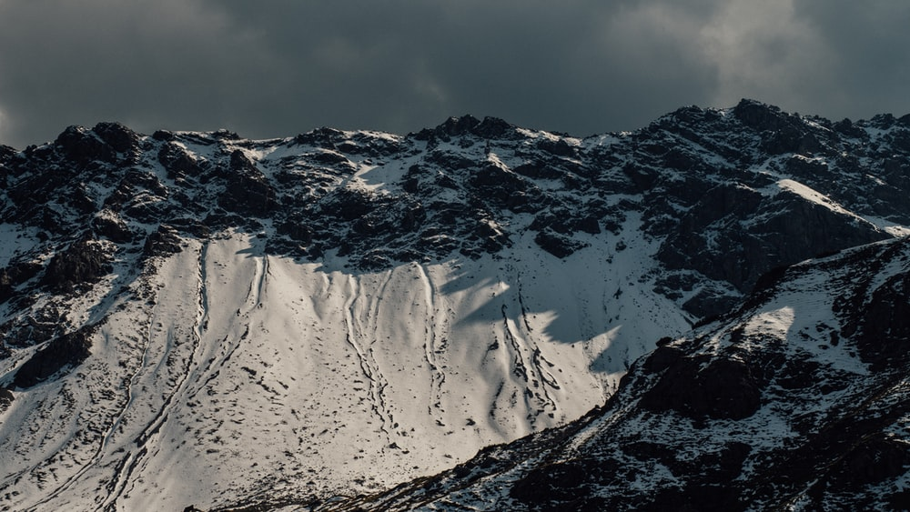 black mountain filled with snow during daytime