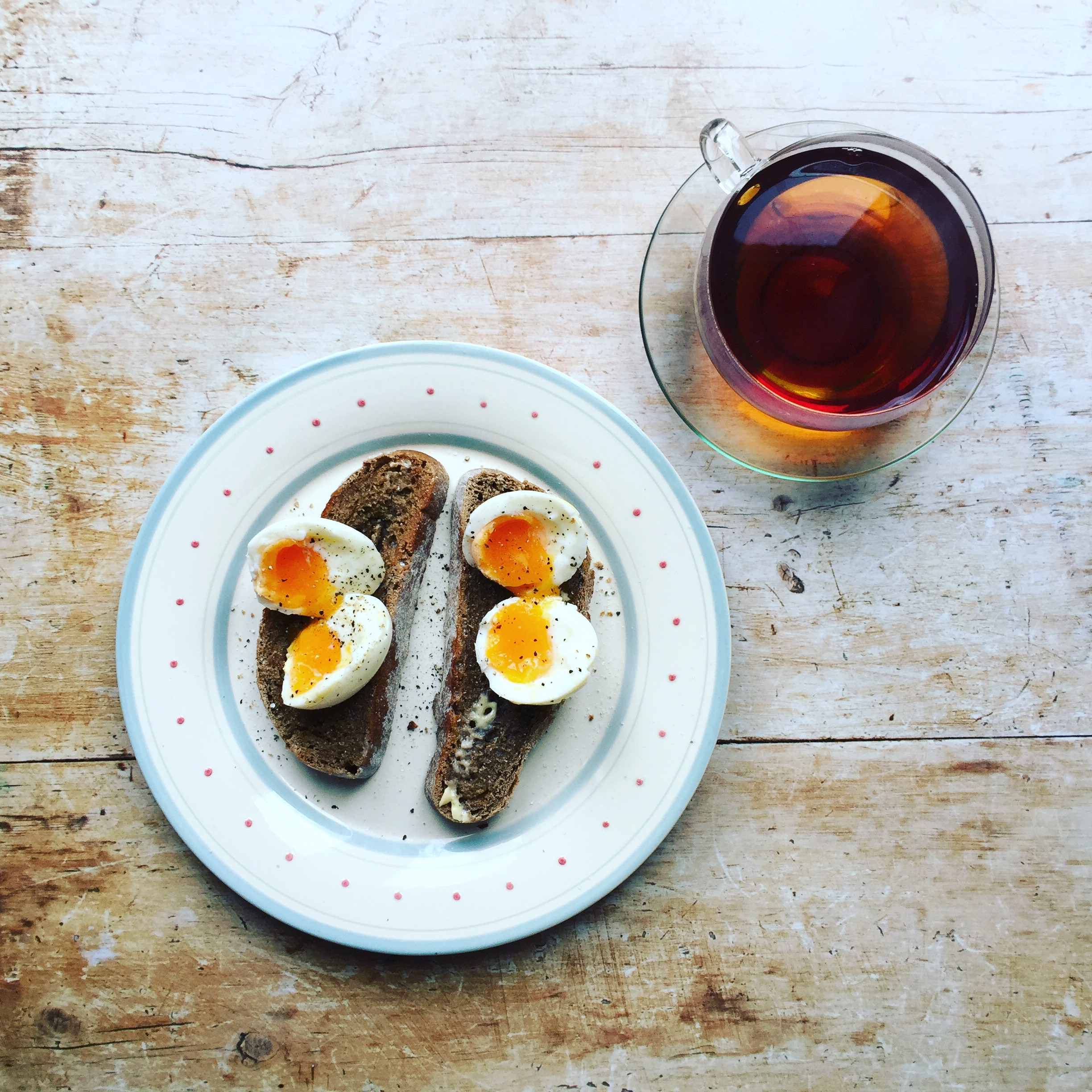 boiled eggs and toast on white ceramic plate near clear glass teacup filled with brown liquid