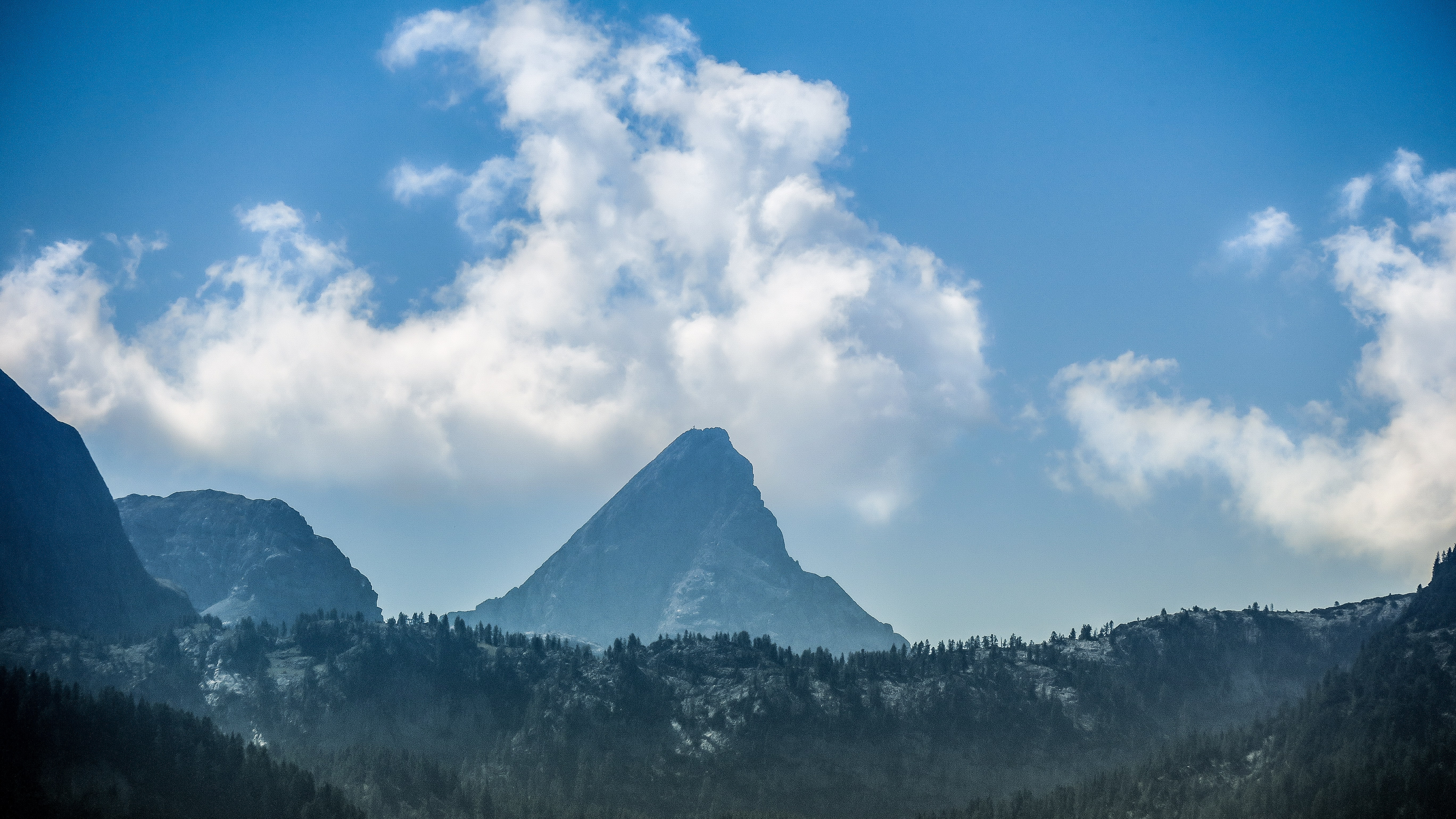 landscape photography of mountains under white clouds