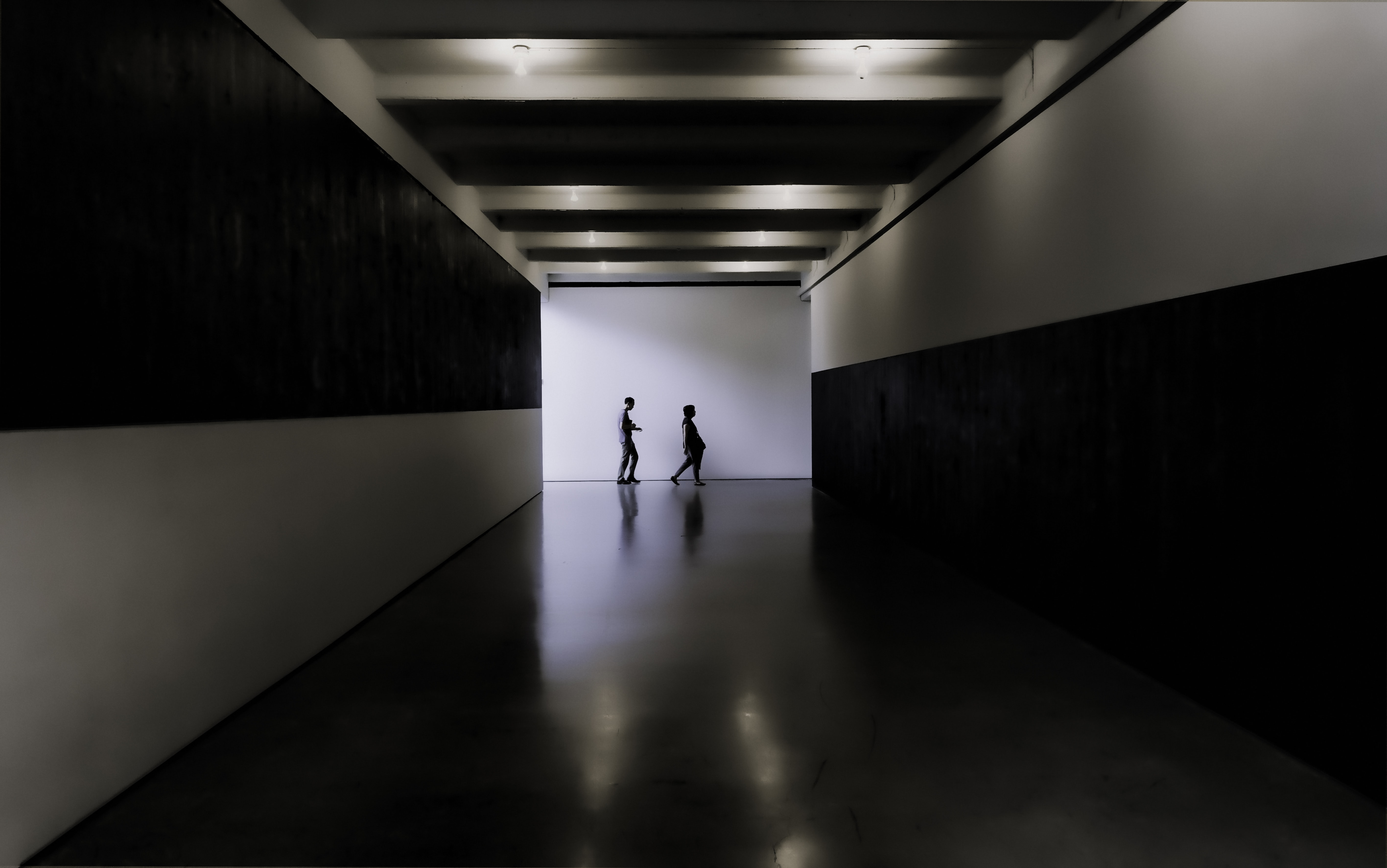 two persons walking towards white and black building