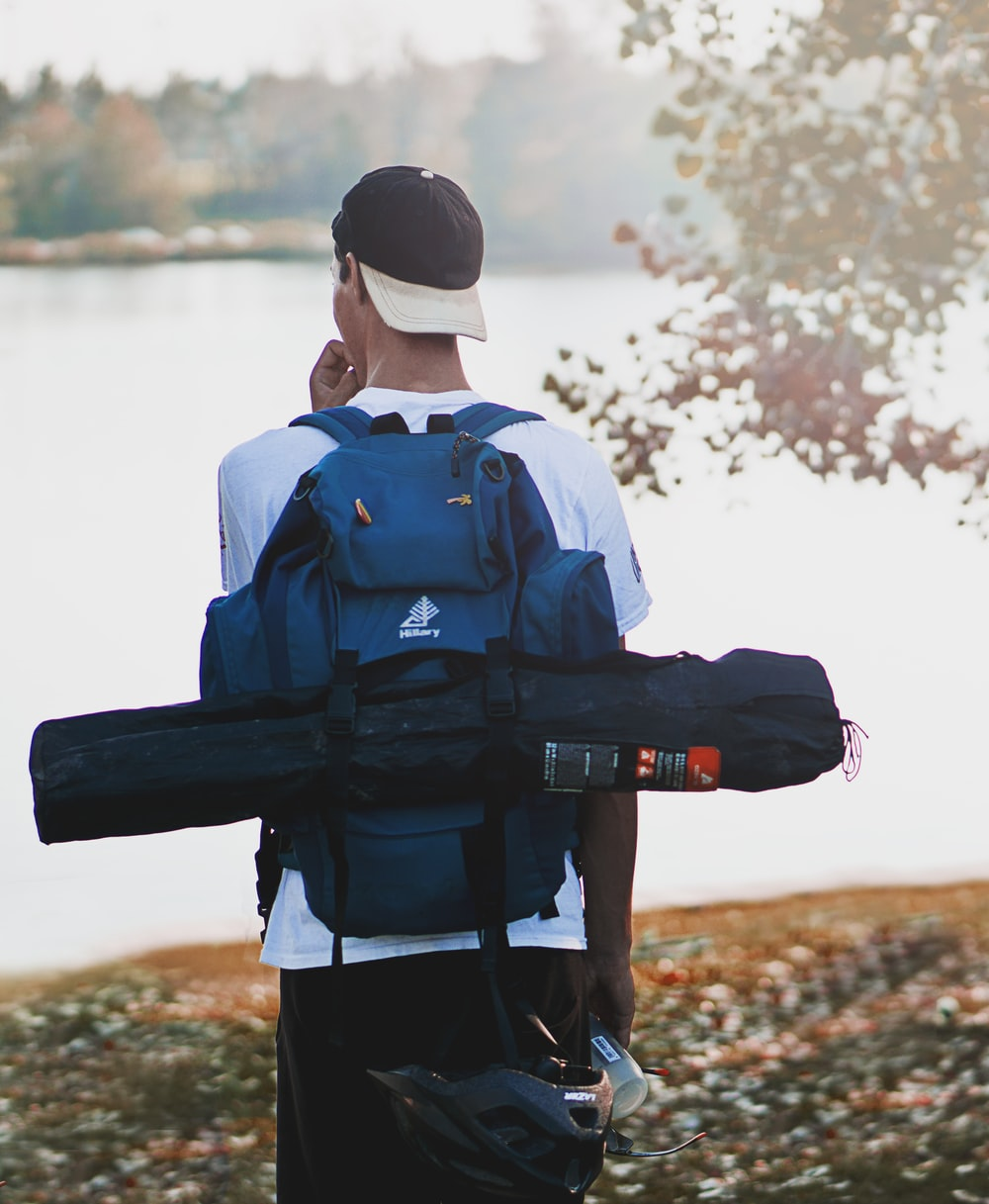 man wearing hiking backpack and tent bag standing near calm body of water