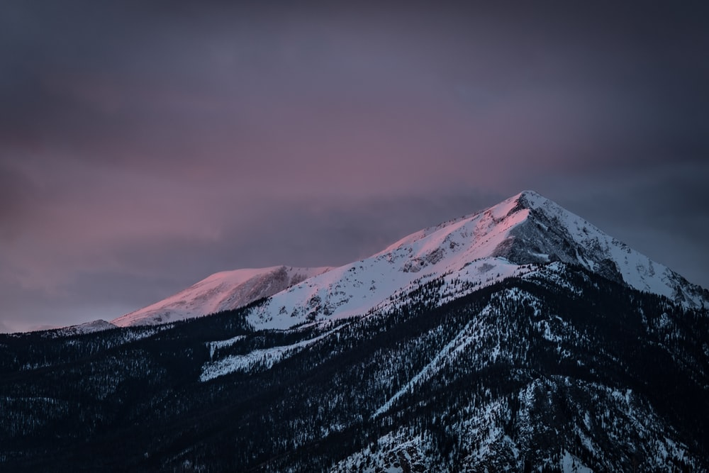 snow capped mountain during black cloudy day