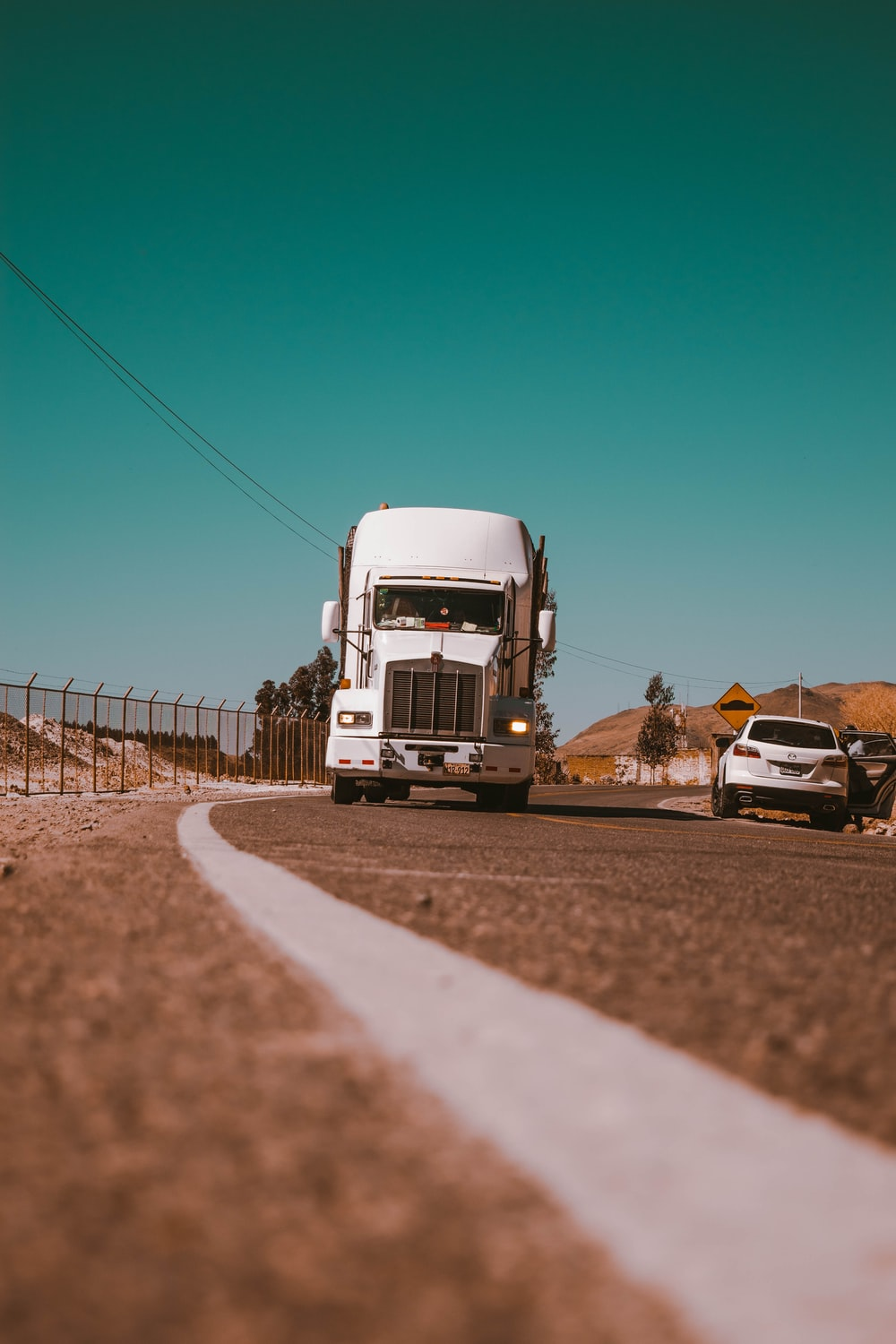 white freight truck on grey concrete road