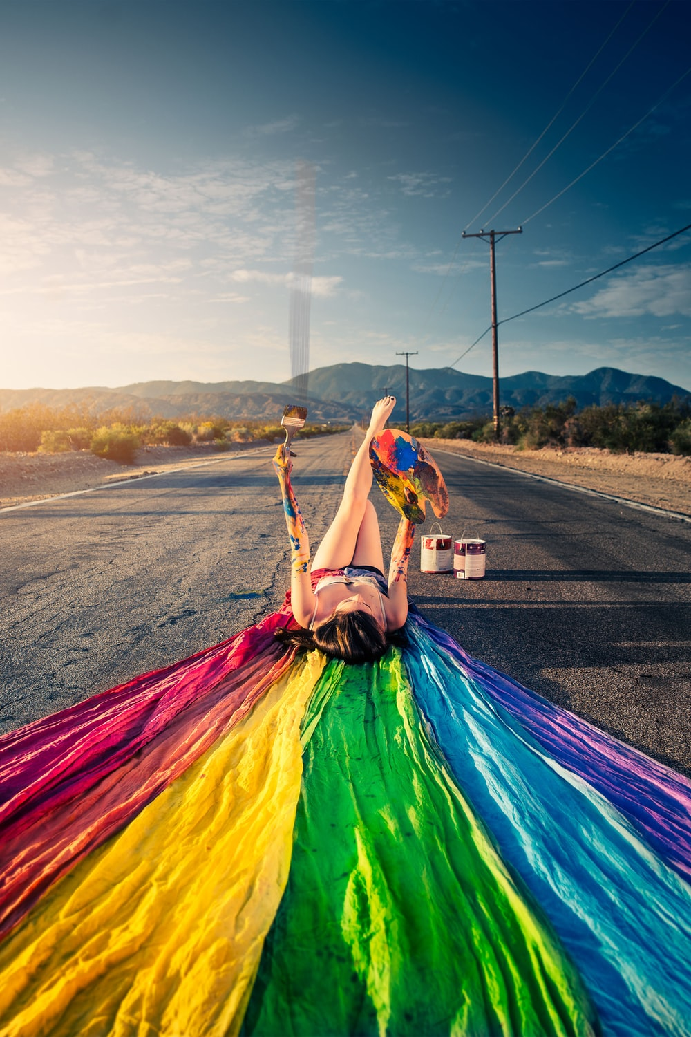 woman lying on road with multicolored textile during daytime