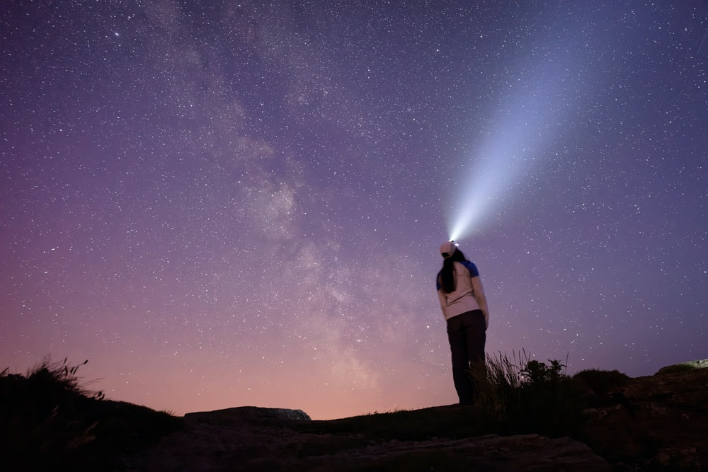woman wearing headlamp standing on hilltop during nighttime