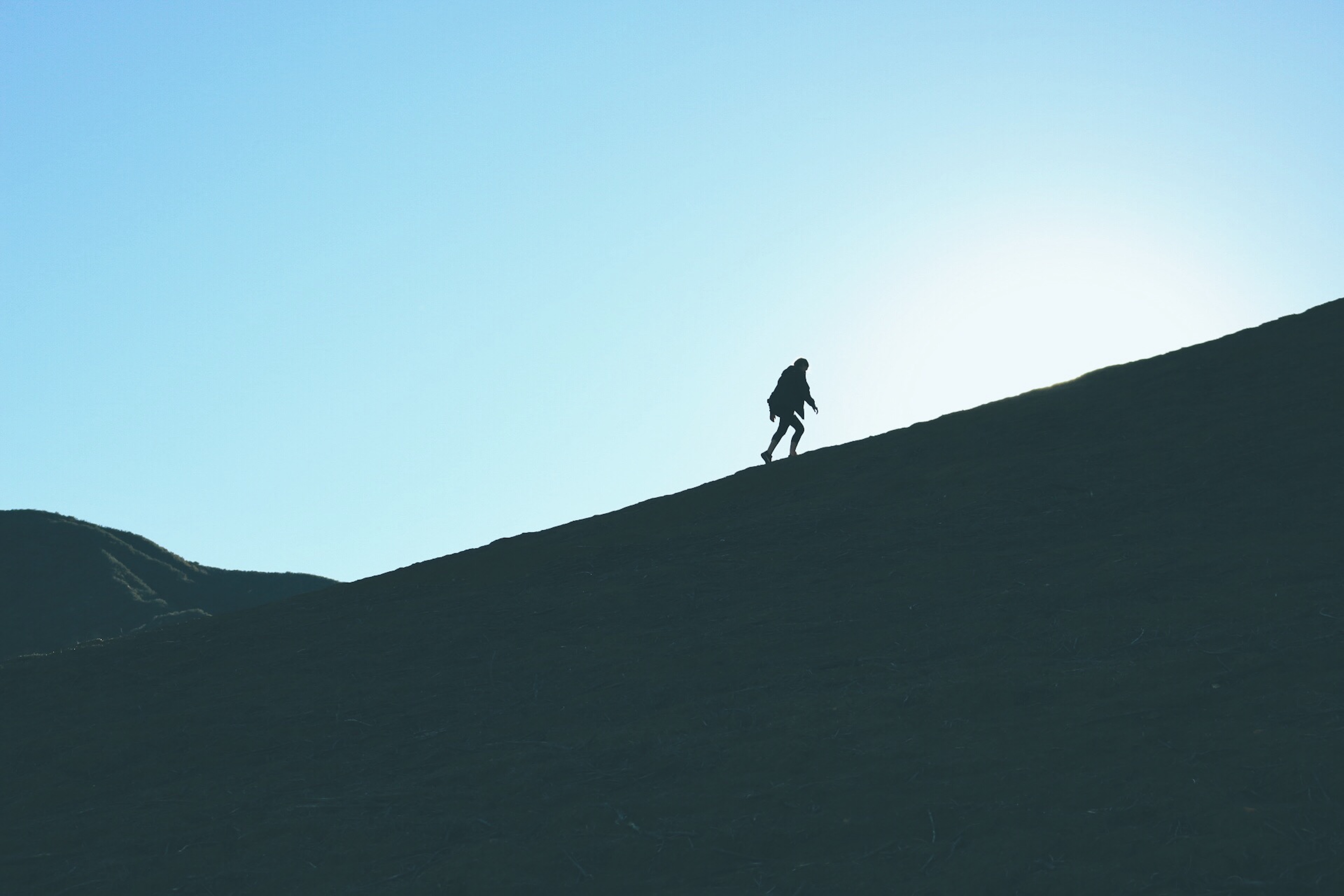 silhouette of man climbing hill