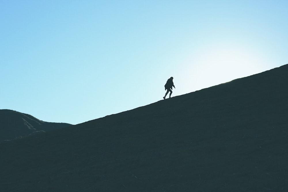 silhouette of man climbing hill