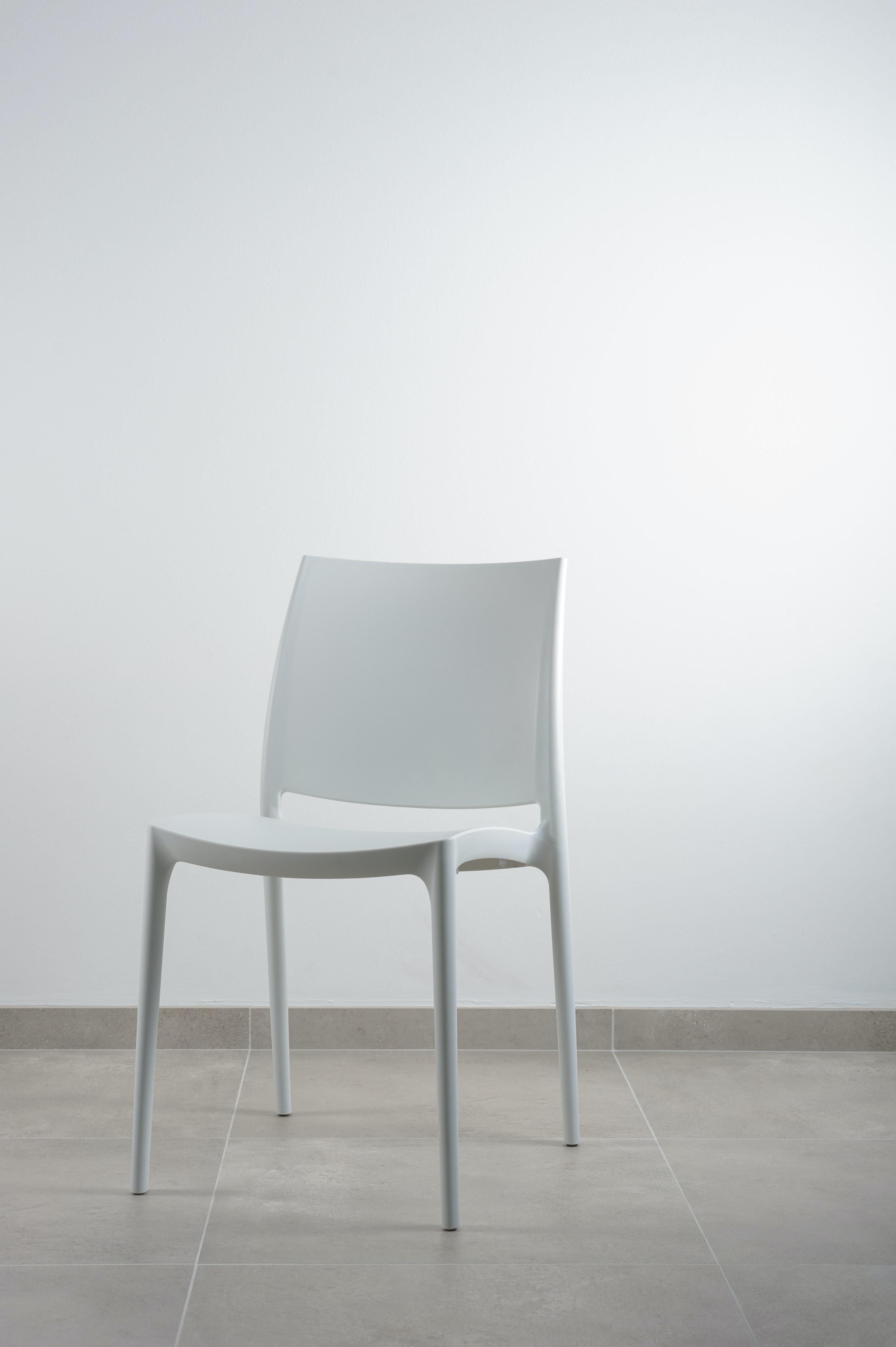 White Armless Chair Near White Wall