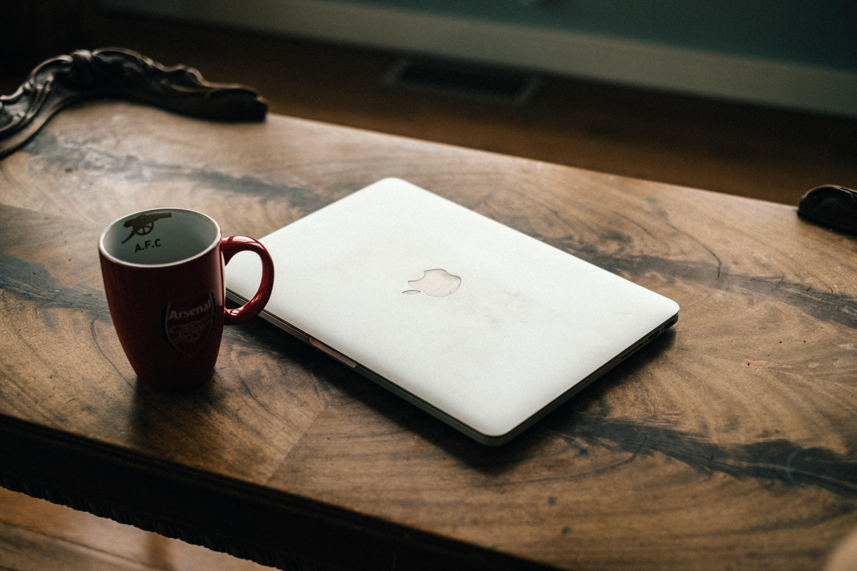 silver MacBook near red ceramic mug