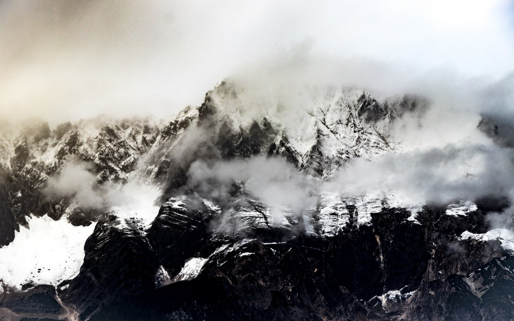 mountain ranges covered in snow and white fog