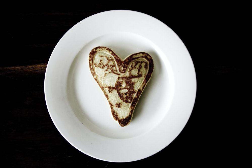 heart-shaped toasted bread on round white ceramic plate