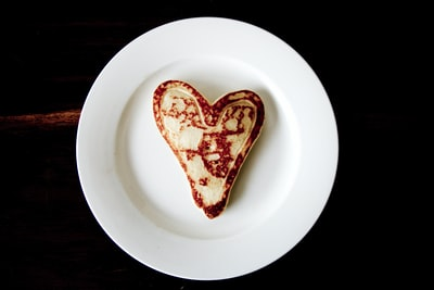 heart-shaped toasted bread on round white ceramic plate plate teams background