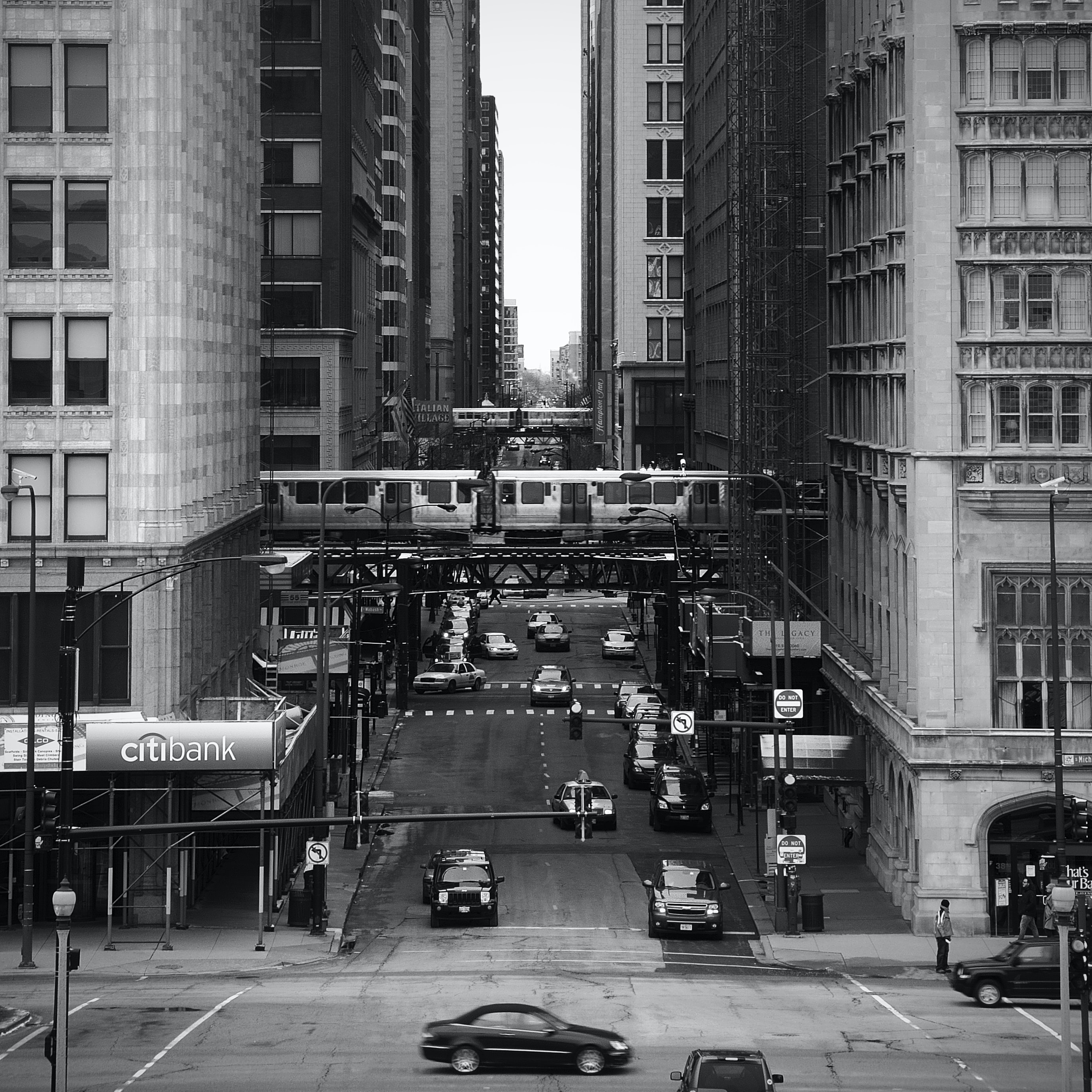grayscale photography of vehicles between high rise buildings