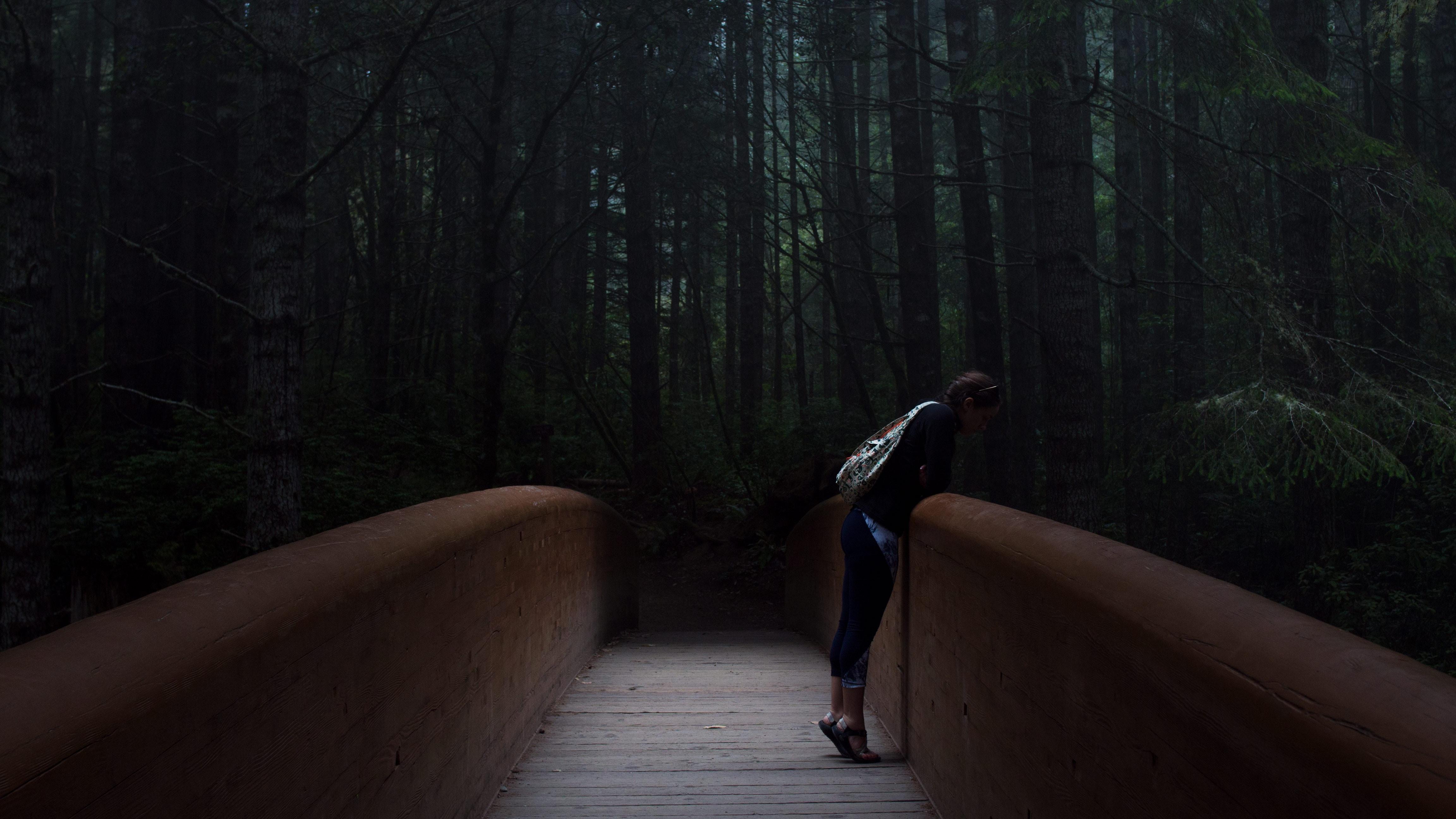 woman standing on brown bridge leaning forward
