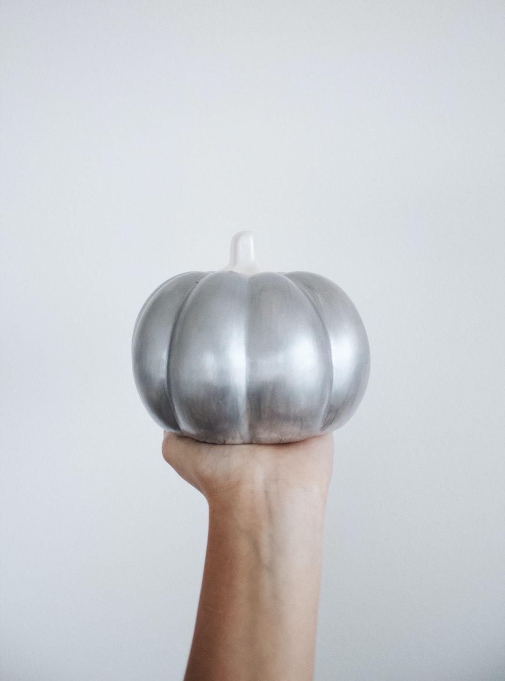 person holding silver round ornament