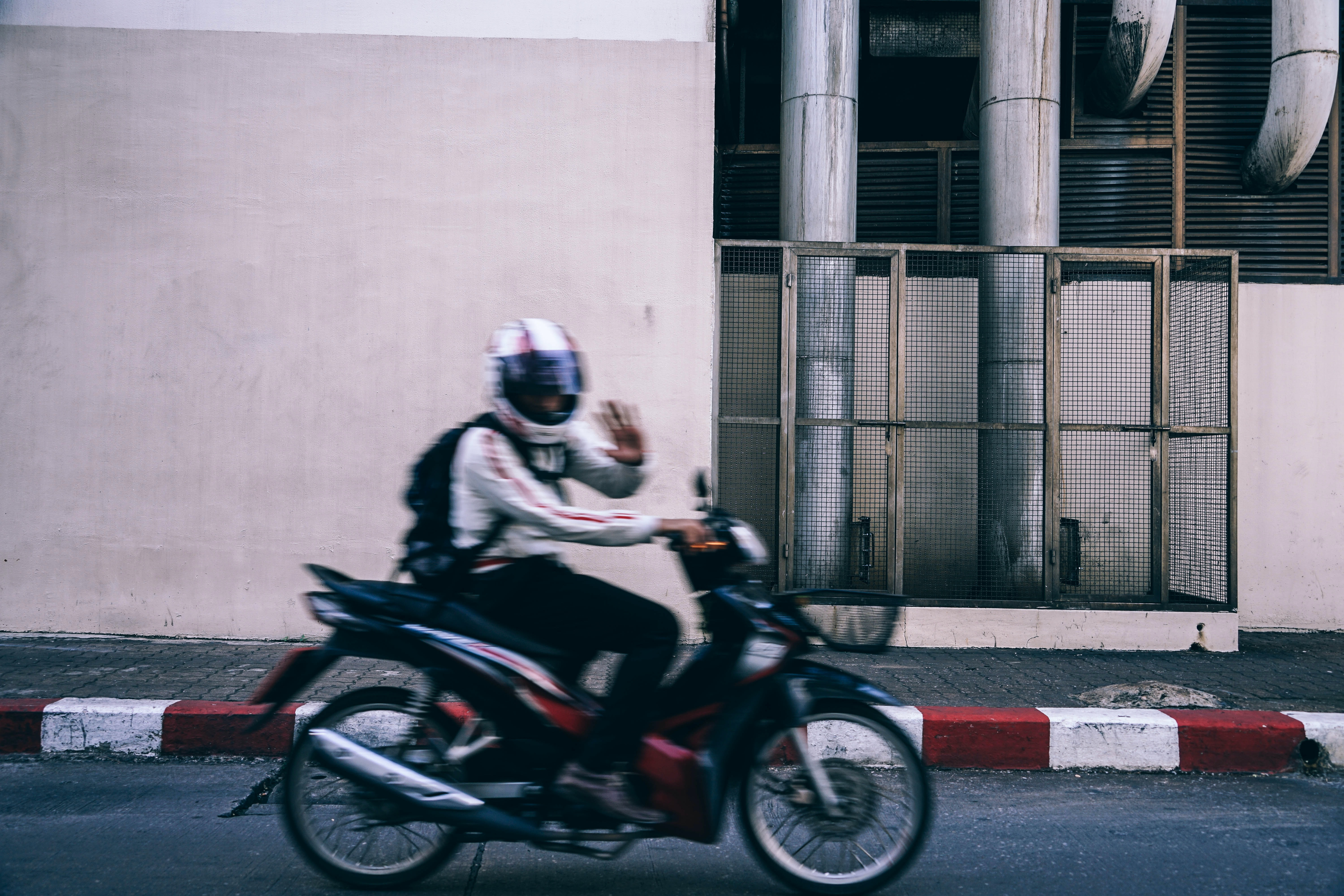 person riding underbone motorcycle waving left hand