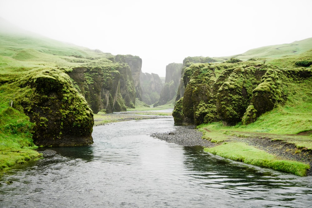 landscape photography of river between green mountains