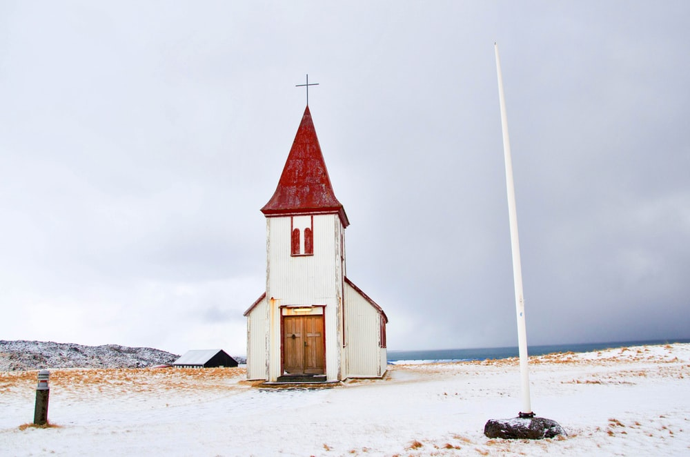 white pole near white and red chapel
